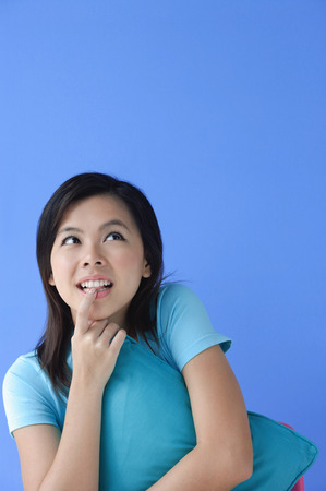 Young woman hugging pillow, biting finger Stock Photo