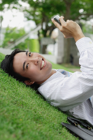 Businessman lying on grass in park, holding mobile phone, smiling at camera