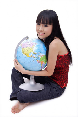 Young woman sitting on floor, embracing globe, smiling at camera