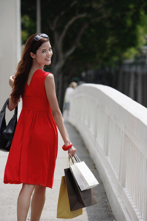 shoulder carrying: Woman in red dress carrying shopping bags, looking over shoulder LANG_EVOIMAGES
