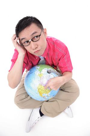 world at your fingertips: Man sitting on floor, holding globe, thinking