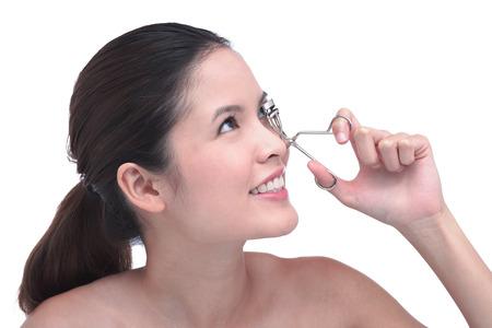 Young woman using eyelash curler