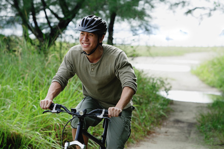 Man cycling on nature path, smiling