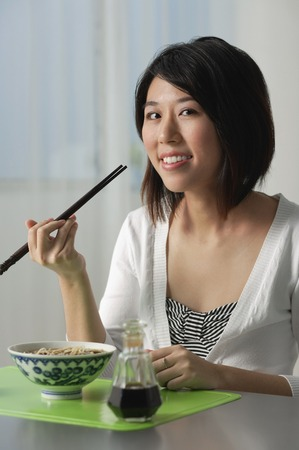 Young woman with chopsticks, eating a bowl of noodles