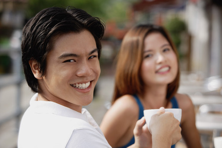 focus in foreground: Couple in cafe having coffee, focus on man in foreground, smiling at camera