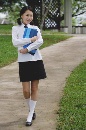 Young woman in school uniform, walking on path, smiling at camera