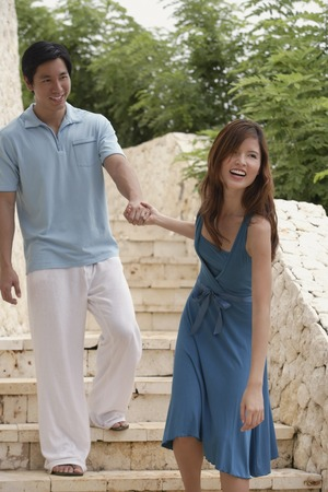 down the stairs: Couple walking down stairs, woman pulling man