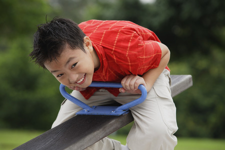 Boy sitting on See-Saw in playground