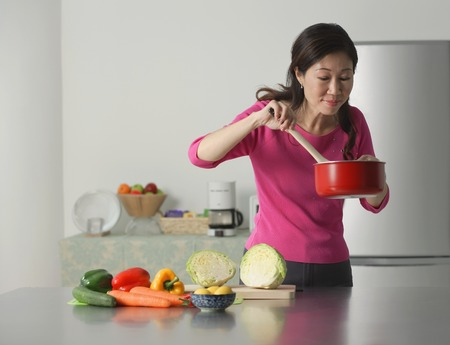 Mature woman cooking in kitchen, looking at contents of pot