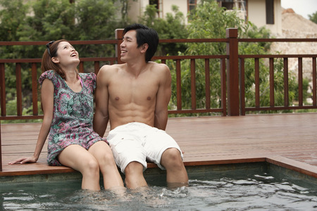 ankle deep in water: Couple sitting at the edge of swimming pool