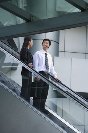 together with long tie: Businessman and businesswoman on escalator LANG_EVOIMAGES