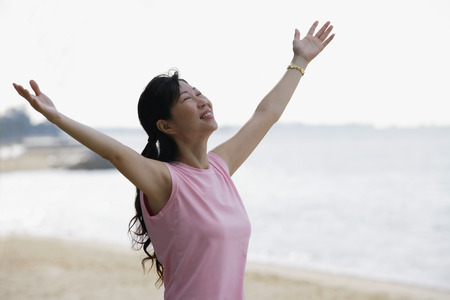 Woman standing on beach, looking up, arms outstretched