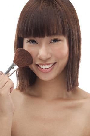 blusher: Young woman applying blusher LANG_EVOIMAGES