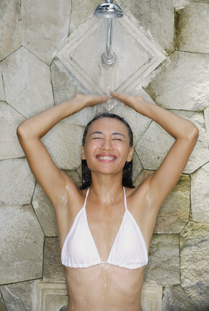 Young woman in white bikini, taking a shower