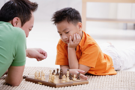 9 10 years: Father and son lying on floor, playing chess LANG_EVOIMAGES