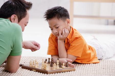 pantalones abajo: Padre e hijo acostado en el piso, jugando al ajedrez
