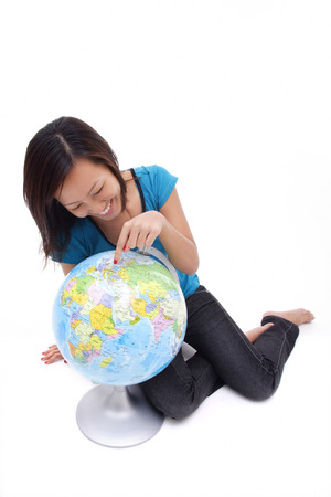 world at your fingertips: Woman pointing at globe