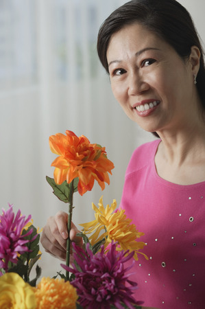 Mature woman holding flowers, smiling at camera, portrait Stock Photo