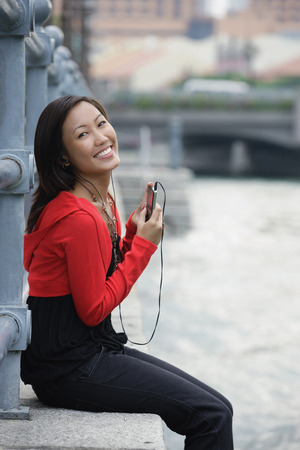 Woman sitting by river, listening to MP3 player, portrait