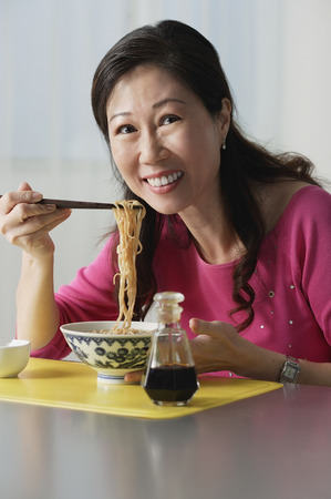 Mature woman eating a bowl of noodles
