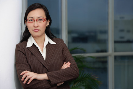 Businesswoman leaning on wall, arms crossed Stock Photo