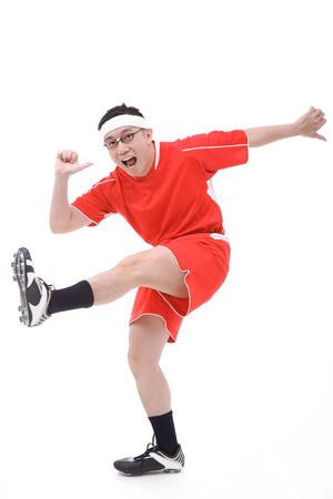 kicking: Man in soccer uniform, kicking leg in air