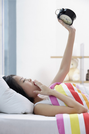 Young woman lying on bed, looking at alarm clock, hand on mouth LANG_EVOIMAGES
