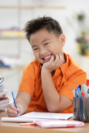 9 10 years: Boy doing homework, smiling at camera, hand on chin