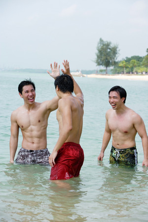 Three men standing waist deep in sea 版權商用圖片
