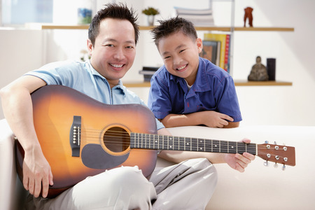 9 10 years: Father and son smiling at camera, father holding guitar
