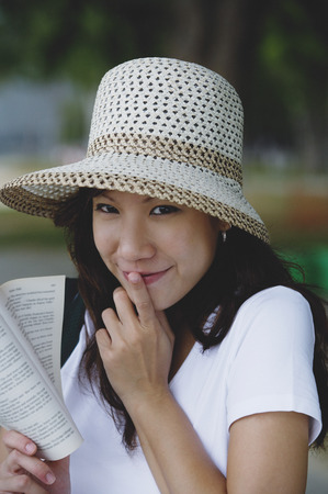 Young woman wearing hat, holding book, finger on mouth