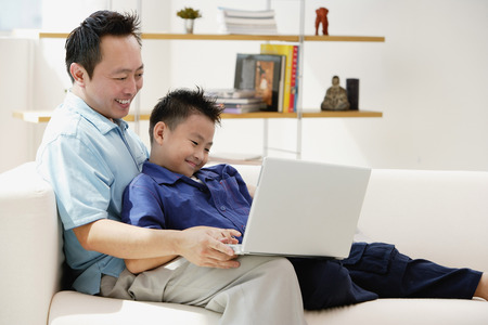 9 10 years: Father and son in living room, looking at laptop LANG_EVOIMAGES