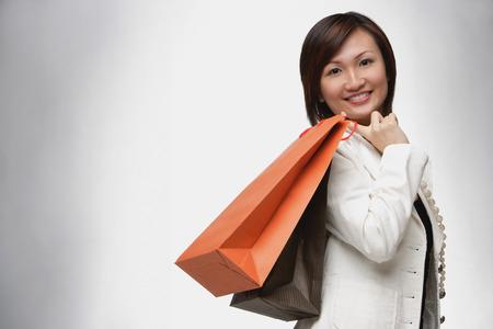 over the shoulder: Businesswoman carrying shopping bags over shoulder, smiling LANG_EVOIMAGES