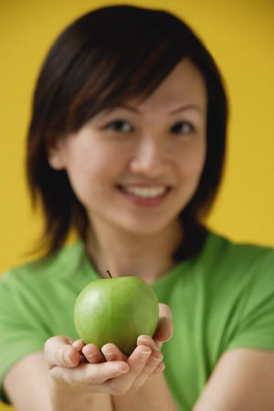 cupped: Young woman holding apple  in cupped hands LANG_EVOIMAGES