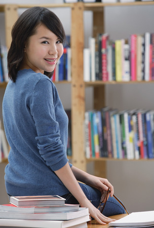 over the shoulder: Young woman in library, sitting on table, looking over shoulder at camera LANG_EVOIMAGES