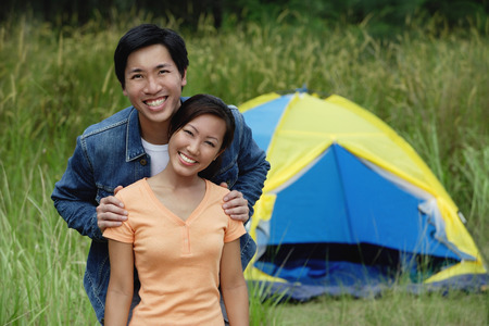Couple with tent in the background, portrait