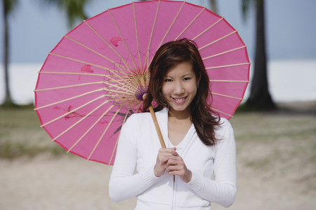 Young woman using pink umbrella