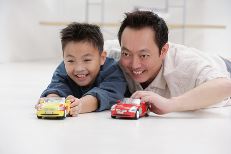 9 10 years: Father and son lying on floor, playing with toy cars