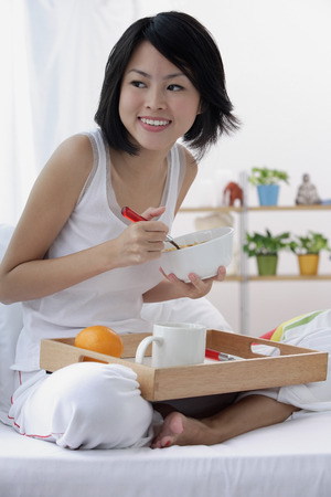 Young woman having breakfast in bed Stock Photo