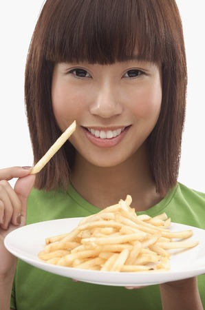 Young woman holding a plate of French fries LANG_EVOIMAGES
