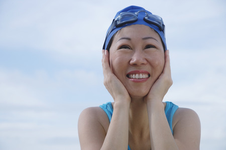 Mature woman wearing swim cap and goggles, hands on face, looking away