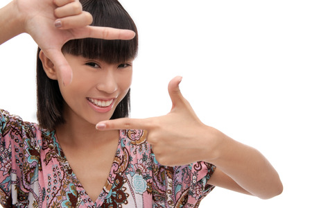 Young woman smiling at camera, making finger frame