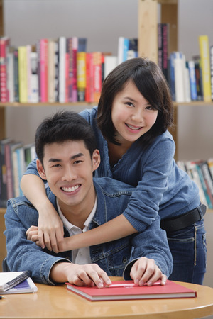Couple in library, woman embracing man from behind LANG_EVOIMAGES