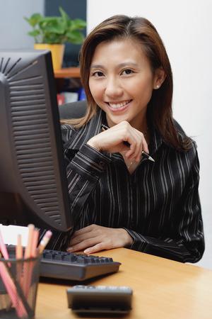 Female executive at desk, hand on chin, smiling at camera