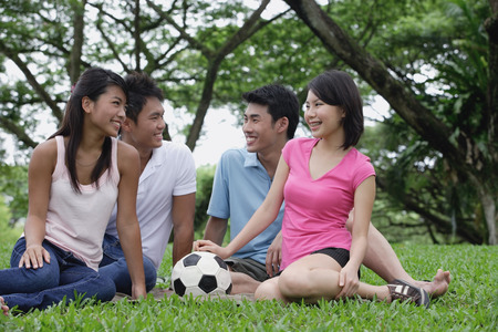 adults: Young adults sitting in park LANG_EVOIMAGES