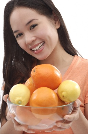 Young woman holding bowl of oranges and lemons Stock Photo