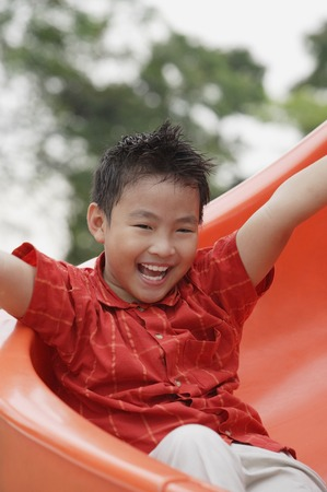 9 10 years: Boy coming down playground slide, arms outstretched, smiling LANG_EVOIMAGES