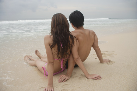 Couple sitting on beach, looking out to sea