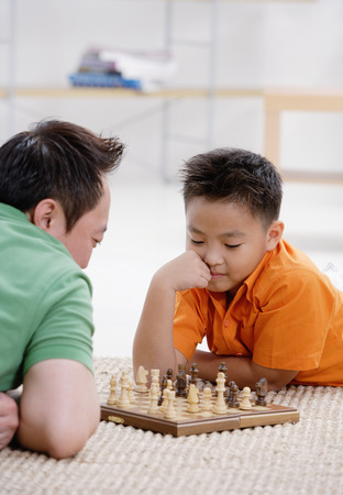 9 10 years: Father and son at home, playing chess LANG_EVOIMAGES