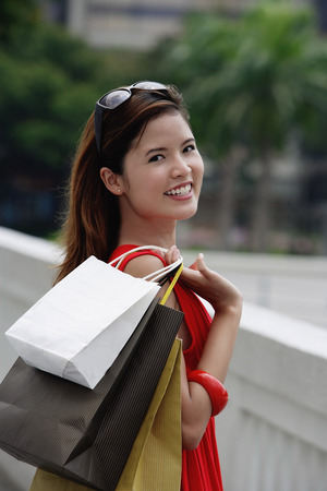 over the shoulder: Woman carrying shopping bags over shoulder